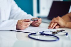 Doktorn konsulterar med hans patient i en medicinsk klinik arkivfoto