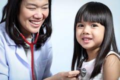 Doktorn kontrollerade barnflickans kropp Fotografering för Bildbyråer