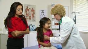Doktorn kontrollerar andning av det sjuka lilla latinamerikanska barnet lager videofilmer