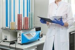 Doktorn kontrollerar datan i tidskriften, mot bakgrunden av petri disk Fotografering för Bildbyråer