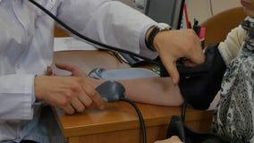 Doktorn mäter arteriellt blodtryck av flickapatienten vid tonometer i klinik stock video