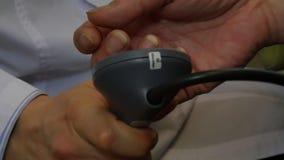 Doktorn mäter arteriellt blodtryck av patienten vid tonometer i klinik arkivfilmer