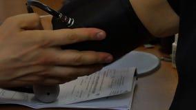Doktorn mäter arteriellt blodtryck av patienten vid tonometer i klinik lager videofilmer