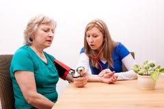 Doktorn mäter den höga vuxna människan blodtrycket Arkivbild