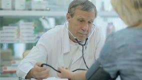 Doktorn mäter trycket av en kvinna i a lager videofilmer