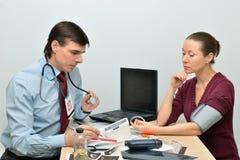 Doktorn mäter trycket av en kvinna till patienten arkivfoton