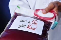 Doktorn med en blodpåse med textkassaskåpet per liv ger blod Arkivfoton