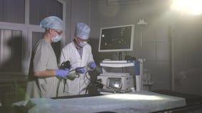 Doktorn och assistentdoktorn förbereder medicinsk utrustning för arbete arkivfilmer