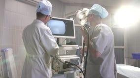 Doktorn och hans assistent förbereder medicinsk utrustning för operationen i fungeringsrummet lager videofilmer