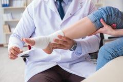Doktorn och patienten under kontrollen-upp för skada i sjukhus royaltyfri fotografi