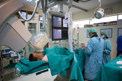 Doktorn och personalen behandlar med Angiography Arkivfoto