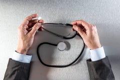Doktorn räcker i reflexionen som rymmer en stetoskop för klinisk behandling Arkivbild