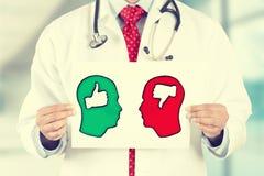 Doktorn räcker det hållande kortet med tummar upp symboler för tummar ner inom tecken som formas som det mänskliga huvudet Arkivbild