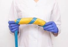 Doktorn rymmer bananen i hand med att mäta bandet Begrepp av den ökande manliga penisen och operationen, manligt organ för förhöj royaltyfri fotografi