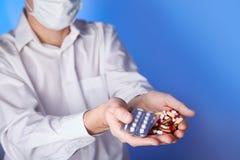 Doktorn rymmer denfärgade piller och packen av olika minnestavlablåsor i händer Universalmedel livräddningservice, ordinerar medi royaltyfri bild
