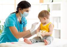 Doktorn rymmer en injektionvaccinering barnet royaltyfri bild