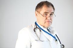 Doktorn ser framåtriktat och att skjuta hans exponeringsglas till spetsen av hans näsa, en stetoskop och ett emblem som hänger fr royaltyfri foto
