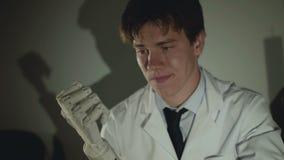 Doktorn ser på en handimplantat och tänker i regeringsställning 4K stock video