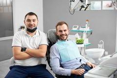 Doktorn sitter bredvid tillfredsställd patient i tand- stol royaltyfria foton