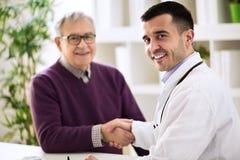 Doktorn skakar händer med en patient royaltyfria bilder