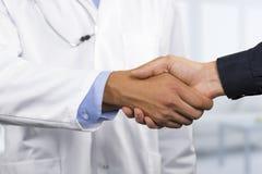Doktorn skakar händer med en patient arkivbild