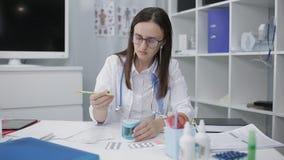 Doktorn skriver en receptbehandling med en blyertspenna Doktorn sätter in en blyertspenna in i en elektronisk vässare stock video