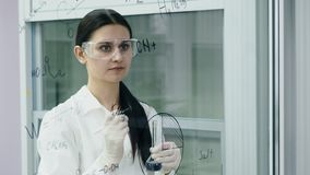 Doktorn skriver vetenskapligt experiment på brädet lager videofilmer