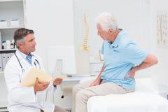 Doktorn som diskuterar rapporter med tålmodigt lidande från tillbaka, smärtar Arkivbild