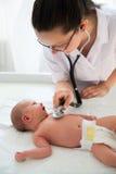 Doktorn som undersöker, behandla som ett barn flickan Arkivbild