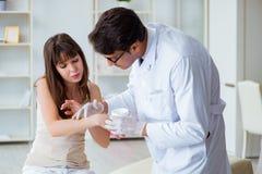 Doktorn som undersöker huden av den kvinnliga patienten royaltyfri fotografi