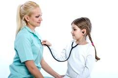 Doktorn spelar med flicka-patienten som låter henne lyssna till henne Royaltyfri Bild