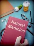 Doktorn stöttar en bok av naturlig medicin i ett medicinskt laboratorium arkivbild