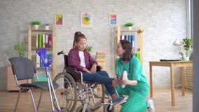 Doktorn undersöker benet av en tonårs- flicka med ett handikapp i en rullstol stock video