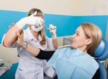 Doktorn undersöker det muntliga hålet på tandförfall Kariesskydd Behandling för tandförfall Doktorn sätter injektionen till Arkivbild