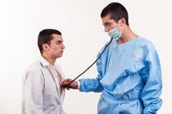 Doktorn undersöker en patient för ung man med stetoskopet Fotografering för Bildbyråer