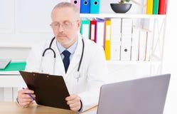 Doktorn undersöker en patients sjukdomshistoria i en klinik royaltyfria foton