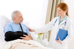 doktorn undersöker pensionären för kvinnligsjukhustålmodign Arkivbild