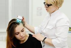 Doktorn undersöker skalperar en special apparat med en UV lampa Arkivfoton