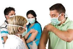Doktorn vaccinerar gruppfolk Royaltyfri Bild