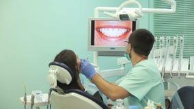 Doktorn visar på bildskärmen de sunda tänderna av patienten stock video