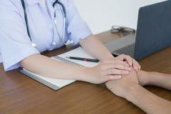 Doktorns hand gör det manliga tålmodiga säkert arkivfoto