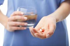 Doktors händer som rymmer två preventivpillerar och ett exponeringsglas av vatten royaltyfri bild