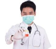 Doktors hand som rymmer en flaska av den blodiga urinprövkopian Royaltyfri Foto