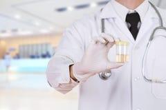 Doktors hand som rymmer en flaska av urinprövkopian i sjukhus Royaltyfri Foto