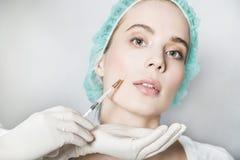 Doktorsaestheticianen gör framsidaskönhetinjektioner till den kvinnliga patienten Fotografering för Bildbyråer