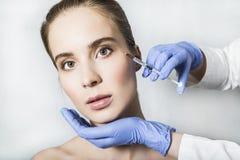 Doktorsaestheticianen gör framsidaskönhetinjektioner till den kvinnliga patienten Royaltyfria Foton