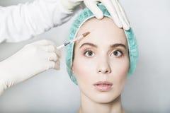 Doktorsaestheticianen gör framsidaskönhetinjektioner till den kvinnliga patienten Arkivbild