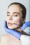 Doktorsaestheticianen gör kantkorrigering och stigande till den kvinnliga patienten Arkivfoto