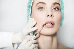 Doktorsaestheticianen gör kantkorrigering och stigande till den kvinnliga patienten Arkivbilder
