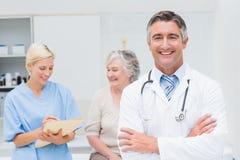 Doktorsanseendearmar korsade med sjuksköterskan och patienten i bakgrund Royaltyfri Bild